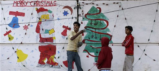 A Pakistani reacts while painting a depiction of a Santa Claus and a Christmas tree on a wall in a Christian neighborhood in Islamabad, Pakistan, Friday, Dec. 23, 2011. &#40;AP Photo&#47;Muhammed Muheisen&#41; <span class=meta>(AP Photo&#47; Muhammed Muheisen)</span>