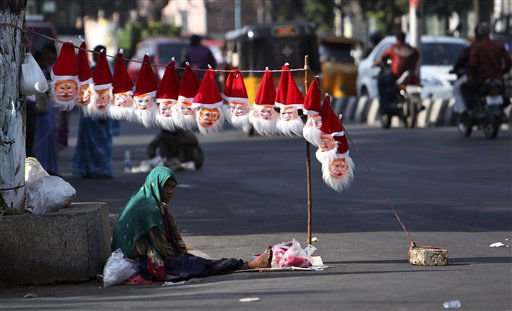 An Indian street vendor selling Santa Claus masks waits for customers ahead of Christmas on a road in Hyderabad, India, Friday, Dec.23, 2011. Christmas day is observed as a national holiday in India. &#40;AP Photo&#47;Mahesh Kumar A.&#41; <span class=meta>(AP Photo&#47; Mahesh Kumar A)</span>