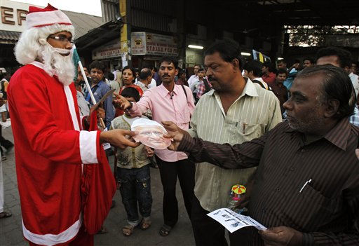 A supporter of popular Indian anti-corruption activist, Anna Hazare, dressed as Santa Claus distributes pamphlets of corruption campaign outside a rail station in Mumbai, India, Saturday, Dec. 24, 2011. Christmas Day is observed as a national holiday in India. &#40;AP Photo&#47;Rafiq Maqbool&#41; <span class=meta>(AP Photo&#47; Rafiq Maqbool)</span>