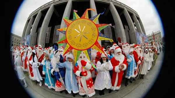 In this photo taken with a fisheye lens, men wearing Ded Moroz &#40;Grandfather Frost&#41; costumes, &#40;the Santa Claus in Russia, Belarus and Ukraine,&#41; and women wearing Snegurochka &#40;Snow Maiden&#41; costumes, the traditional companion of Ded Moroz, perform at the central square in Minsk, Belarus, Saturday, Dec. 24, 2011. &#40;AP Photo&#47;Sergei Grits&#41; <span class=meta>(AP Photo&#47; Sergei Grits)</span>