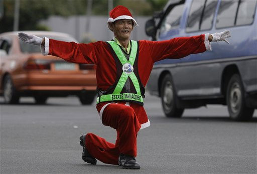 "<div class=""meta ""><span class=""caption-text "">Filipino traffic enforcer Ramiro Hinojas dressed in a Santa Claus costume kneels down to direct the flow of vehicles in a dancing way along a busy intersection on Christmas eve in suburban Pasay, south of Manila, Philippines, Saturday Dec. 24, 2011. Christmas is one of the most important holidays in this predominantly Roman Catholic nation. (AP Photo/Aaron Favila) (AP Photo/ Aaron Favila)</span></div>"