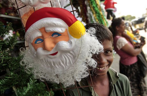 A Sri Lankan street child reacts to the camera as he stands next to a mask of Santa Claus in Colombo, Sri Lanka, Saturday, Dec. 24, 2011. Christmas Day is observed as a national holiday in India. &#40;AP Photo&#47;Eranga Jayawardena&#41; <span class=meta>(AP Photo&#47; Eranga Jayawardena)</span>