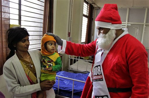 An Indian man dressed as Santa Claus blesses a child patient during Christmas celebrations at a hospital in Ahmedabad, India, Saturday, Dec. 24, 2011. Christmas Day is observed as a national holiday in India. &#40;AP Photo&#47;Ajit Solanki&#41; <span class=meta>(AP Photo&#47; Ajit Solanki)</span>
