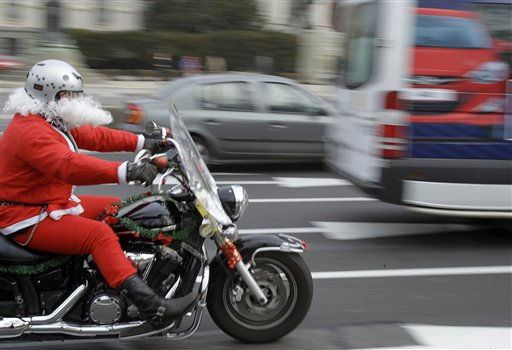 A motorcyclist wearing a Santa Claus suit rides in downtown Belgrade, Serbia, Saturday, Dec. 24, 2011. Some 250 bikers brought presents to patients at a children&#39;s hospital in Belgrade. &#40;AP Photo&#47;Darko Vojinovic&#41; <span class=meta>(AP Photo&#47; Darko Vojinovic)</span>