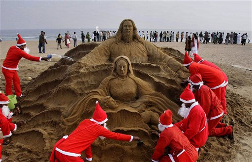 "<div class=""meta ""><span class=""caption-text "">Artists dressed as Santa Claus create a Santa Claus sculpture on the eve of Christmas Puri golden beach, 67 kilometers (42 miles) from the eastern city of Bhubaneswar, India, Saturday, Dec. 24, 2011. Christmas Day is observed as a national holiday in India. (AP Photo/Biswaranjan Rout) (AP Photo/ Biswaranjan Rout)</span></div>"