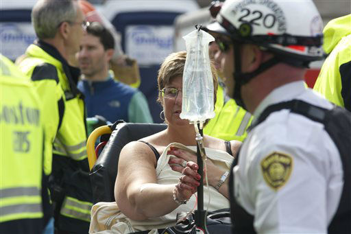 Emergency responders help a woman who was injured in a bomb blast near the finish line of the Boston Marathon Monday, April 15, 2013 in Boston. Two bombs exploded in the packed streets near the finish line of the marathon on Monday, killing at least two people and injuring more than 80, authorities said.  <span class=meta>(AP Photo&#47; Jeremy Pavia)</span>