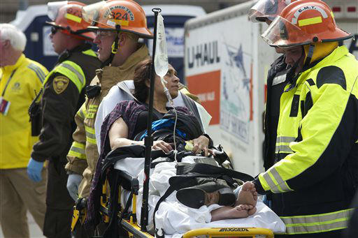 Emergency responders aid a woman on a stretcher who was injured in a bomb blast near the finish line of the Boston Marathon Monday, April 15, 2013 in Boston. Two bombs exploded in the packed streets near the finish line of the marathon on Monday  <span class=meta>(AP Photo&#47; Jeremy Pavia)</span>