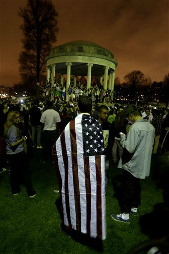 Joe Cesaro, 19, uses a U.S. flag over his back as he joins a crowd gathered at Boston Common after the final suspect in the Boston Marathon bombing was arrested, Friday, April 19, 2013, in Boston. Marathon bombing suspect Dzhokhar Tsarnaev was captured in Watertown, Mass. The 19-year-old college student wanted in the bombings was taken into custody Friday evening after a manhunt that left the city virtually paralyzed and his older brother and accomplice dead.   <span class=meta>(AP Photo&#47; Julio Cortez)</span>