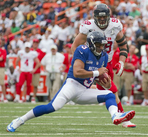 Houston Texans defensive end J.J. Watt &#40;99&#41; of the AFC attempts to chase down Seahawks quarterback Russell Wilson &#40;3&#41; of the NFC in the third quarter of the NFL Pro Bowl football game in Honolulu, Sunday, Jan. 27, 2013. &#40;AP Photo&#47;Eugene Tanner&#41; <span class=meta>(AP Photo&#47; Eugene Tanner)</span>