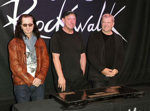 FILE - This Nov. 20, 2012 file photo shows members of the band Rush, from left, Geddy Lee, Neil Peart, and Alex Lifeson at the RockWalk induction of Rush at Guitar Center in Los Angeles. The eclectic group of rockers Rush and Heart, rappers Public Enemy, songwriter Randy Newman, &#34;Queen of Disco&#34; Donna Summer and bluesman Albert King will be inducted into the Rock and Roll Hall of Fame next April in Los Angeles. The inductees were announced Tuesday by 2012 inductee Flea of The Red Hot Chili Peppers at a news conference in Los Angeles. &#40;Photo by Richard Shotwell&#47;Invision&#47;AP, file&#41; <span class=meta>(Photo&#47;Richard Shotwell)</span>