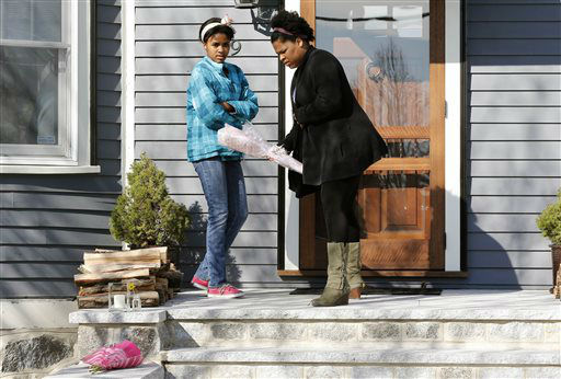 Two women place flowers on the doorstep of the Richard house in the Dorchester neighborhood of Boston, Tuesday, April 16, 2013. Martin Richard, 8, was killed in the Mondays bombings at the finish line of the Boston Marathon. The boy?s mother, Denise, and 6-year-old sister, Jane, were badly injured.   <span class=meta>(AP Photo&#47; Michael Dwyer)</span>