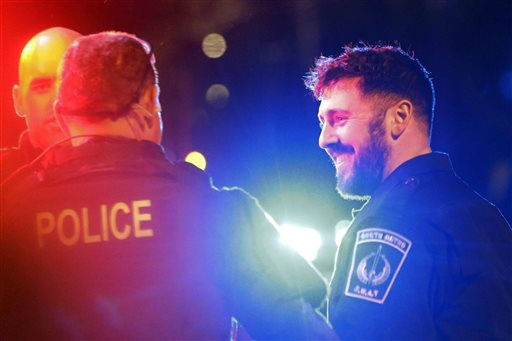 Police officers smile to fellow officers as they leave the scene after the arrest of a suspect of the Boston Marathon bombings in Watertown, Mass., Friday, April 19, 2013. A 19-year-old college student wanted in the Boston Marathon bombings was taken into custody Friday evening after a manhunt that left the city virtually paralyzed and his older brother and accomplice dead.    <span class=meta>(AP Photo&#47; Matt Rourke)</span>