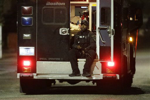 "<div class=""meta ""><span class=""caption-text "">A police officers rides in the back of a van with his weapons out Friday, April 19, 2013, in Watertown, Mass. A tense night of police activity that left a university officer dead on campus just days after the Boston Marathon bombings and amid a hunt for two suspects caused officers to converge on a neighborhood outside Boston, where residents heard gunfire and explosions.  (AP Photo/ Matt Rourke)</span></div>"