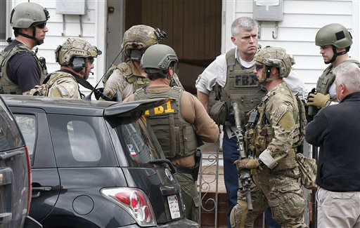 "<div class=""meta image-caption""><div class=""origin-logo origin-image ""><span></span></div><span class=""caption-text"">Heavily armed FBI agents gather next door to 410 Norfolk Street in Cambridge, Mass., Friday, April 19, 2013. Two suspects in the Boston Marathon bombing killed an MIT police officer, injured a transit officer in a firefight and threw explosive devices at police during a getaway attempt in a long night of violence that left one of them dead and another still at large Friday, authorities said as the manhunt intensified for a young man described as a dangerous terrorist.   (AP Photo/ Michael Dwyer)</span></div>"