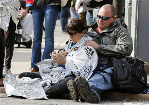 Chris Darmody, right, holds his wife Sue in Boston, Monday, April 15, 2013. Chris says he was waiting for Sue when an explosion detonated near his location at the finish line of the Boston Marathon. The couple were later reunited after all runners were diverted from the course.   <span class=meta>(AP Photo&#47; Michael Dwyer)</span>