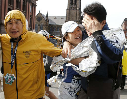 An unidentified Boston Marathon runner, center, is reunited with loved ones near Copley Square following an explosion in Boston Monday, April 15, 2013.  <span class=meta>(AP Photo&#47; Winslow Townson)</span>