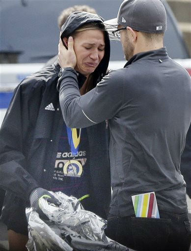 An unidentified Boston Marathon runner is comforted as she cries in the aftermath of two blasts which exploded near the finish line of the Boston Marathon in Boston, Monday, April 15, 2013. &#40;AP Photo&#47;Elise Amendola&#41; <span class=meta>(AP Photo&#47; Elise Amendola)</span>