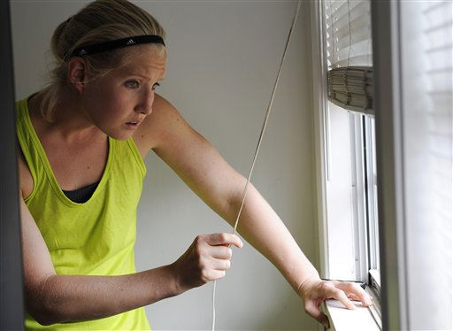 Diana Harbourt looks out her window where a bullet entered during a shootout on her street where three people, including the gunman, were killed, Monday, Aug. 13, 2012, in College Station, Texas. Police say a gunman was being served an eviction notice when he opened fire from inside a home near Texas?A&#38;M and killed a law enforcement officer. &#40;AP Photo&#47;Pat Sullivan&#41; <span class=meta>(AP Photo&#47; Pat Sullivan)</span>