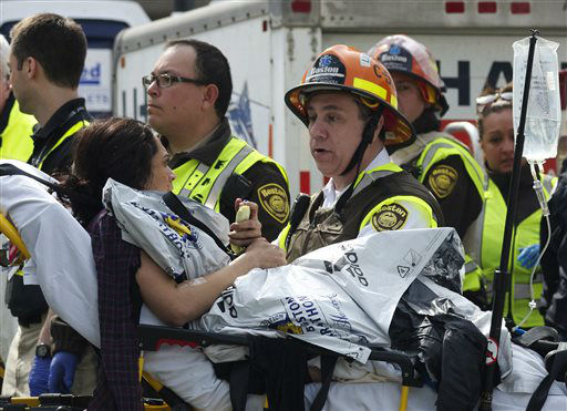 Emergency responders comfort a woman on a stretcher who was injured in a bomb blast near the finish line of the Boston Marathon Monday, April 15, 2013 in Boston. Two bombs exploded in the packed streets near the finish line of the marathon on Monday, killing at least two people and injuring more than 80, authorities said.   <span class=meta>(AP Photo&#47; Jeremy Pavia)</span>