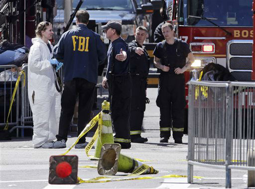 Boston firefighters, right, talk with FBI agents and a crime scene photographer  at the scene of Monday&#39;s Boston Marathon explosions, which killed at least three and injured more than 140, in Boston, Tuesday, April 16, 2013. The bombs that blew up seconds apart near the finish line left the streets spattered with blood and glass, and gaping questions of who chose to attack at the Boston Marathon and why. &#40;AP Photo&#47;Charles Krupa&#41; <span class=meta>(AP Photo&#47; Charles Krupa)</span>
