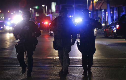 Officers wearing tactical gear arrive at the Watertown neighborhood of Boston, Friday, April 19, 2013. Reports of explosives being detonated and police are telling reporters to turn off their cell phones. Dozens of officers and National Guard members are in Watertown, where television outlets report that gunfire and explosions have been heard.  <span class=meta>(AP Photo&#47; Julio Cortez)</span>