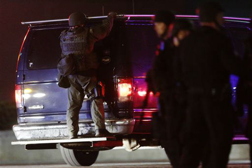 A police officers rides on the back of a van at a staging area as a manhunt is conducted for a suspect Friday, April 19, 2013, in Watertown, Mass. One of two suspects in the Boston Marathon bombing is dead and a massive manhunt is underway for another, authorities said early Friday April 19, 2013. Residents of Watertown, a Boston suburb, have been advised to keep their doors locked and not let anyone in.    <span class=meta>(AP Photo&#47; Matt Rourke)</span>