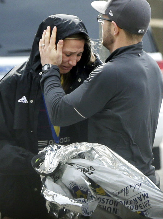 An unidentified Boston Marathon runner is comforted as she cries in the aftermath of two blasts which exploded near the finish line of the Boston Marathon in Boston, Monday, April 15, 2013.  <span class=meta>(AP Photo&#47; Elise Amendola)</span>