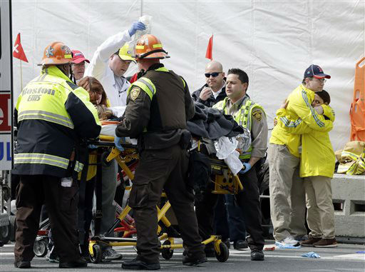 Two Boston Marathon volunteers hug each other, at right, as an injured person is loaded into an ambulance in the aftermath of two blasts which exploded near the finish line of the Boston Marathon in Boston, Monday, April 15, 2013. &#40;AP Photo&#47;Elise Amendola&#41;  <span class=meta>(AP Photo&#47; Elise Amendola)</span>