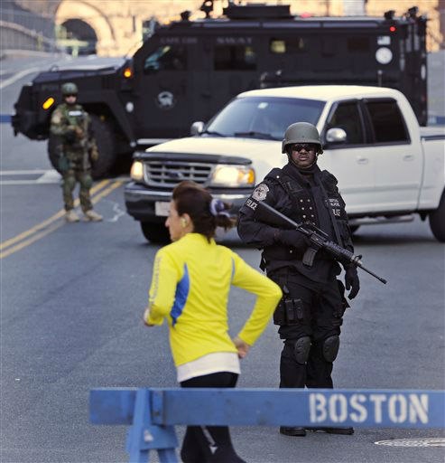"<div class=""meta image-caption""><div class=""origin-logo origin-image ""><span></span></div><span class=""caption-text"">A runner passes a police officer dressed in tactical gear, who blocks a road leading to the Boston Marathon route, the morning after explosions killed three and injured more than 140 in Boston, Tuesday, April 16, 2013. The bombs that blew up seconds apart at the finish line of one of the world's most storied races left the streets spattered with blood and glass, and gaping questions of who chose to attack at the Boston Marathon and why. (AP Photo/Charles Krupa) (AP Photo/ Charles Krupa)</span></div>"
