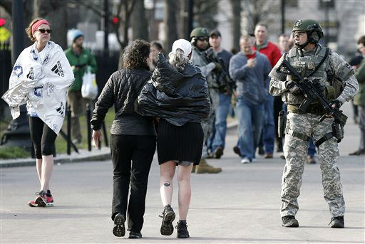 "<div class=""meta ""><span class=""caption-text "">As Boston Marathon runners walk by, SWAT team members stand guard near the finish line in Boston Monday, April 15, 2013. Two explosions shattered the euphoria of the Boston Marathon finish line on Monday, sending authorities out on the course to carry off the injured while the stragglers were rerouted away from the smoking site of the blasts.  (AP Photo/ Winslow Townson)</span></div>"
