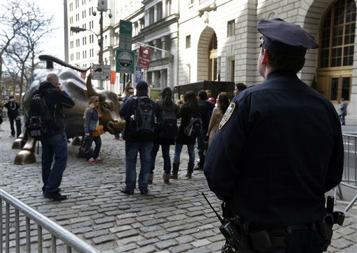A New York City Police officer watches as people take pictures with the bull statue in the Financial District, Tuesday, April 16, 2013 in New York. Law enforcers say New York City remains in a heightened state of alert until more is known about the Boston explosions. More officers are working around New York, including counterterrorism units and beefed up patrols. &#40;AP Photo&#47;Richard Drew&#41; <span class=meta>(AP Photo&#47; Richard Drew)</span>