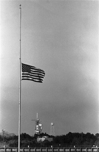 The American flag in the press site at the Kennedy Space Center flies at half-staff at Kennedy Space Center, Florida, Tuesday, Jan. 28, 1986 after NASA officials ordered it lowered following the explosion of the Space Shuttle Challenger. NASA said the crew of seven aboard the craft died in the explosion. Launch pad B is shown under the flag.  <span class=meta>(AP Photo&#47; Jim Cole)</span>