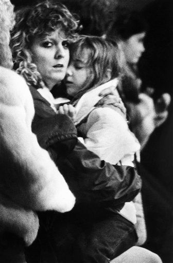 Unidentified woman hugs a child inside the Kimball School in Concord, New Hampshire, Tuesday, Jan. 29, 1986 after the girl returned from the Kennedy Space Center with a group of the classmates of the son of Christa McAuliffe, who was killed in the explosion of the space shuttle Challenger. The children had been up at five in the morning for the launch, and were rushed home after the event turned to disaster. <span class=meta>(AP Photo&#47; Tenenbaum)</span>