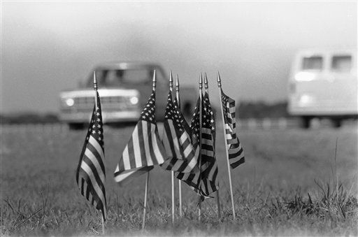 Kennedy Space Center workers en route to Pad 39B were met by the sight of seven small American flags that mysteriously appeared along side the road, Jan. 30, 1986. Seven crew members were killed in the explosion of the Space Shuttle Challenger three days earlier, which was launched from Pad 39B. <span class=meta>(AP Photo&#47; Phil Sandlin)</span>