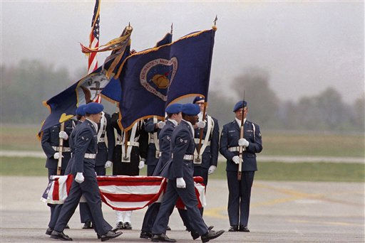 The remains of one of the crew of the Space Shuttle Challenger are carried past an honor guard on the tarmac at Dover Air Force Base in Dover, Delaware on Tuesday, April 29, 1986. The remains of the seven astronauts killed in the January Shuttle explosion were brought to the base to be prepared for burial.