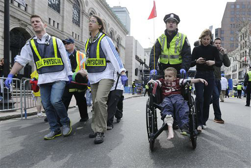 A Boston police officer wheels in injured boy down Boylston Street as medical workers carry an injured runner following an explosion during the 2013 Boston Marathon in Boston, Monday, April 15, 2013. Two explosions shattered the euphoria at the marathon&#39;s finish line on Monday, sending authorities out on the course to carry off the injured while the stragglers were rerouted away from the smoking site of the blasts. &#40;AP Photo&#47;Charles Krupa&#41; <span class=meta>(AP Photo&#47; Charles Krupa)</span>