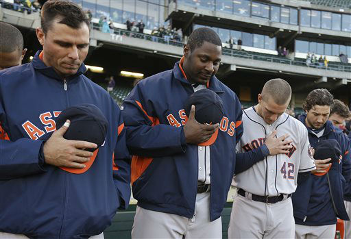 Members of the Houston Astros including Chris Carter, center, observe a moment of silence for the victims involved in an explosion at the Boston Marathon prior to the baseball game against the Oakland Athletics on Monday, April 15, 2013, in Oakland, Calif.   <span class=meta>(AP Photo&#47; Ben Margot)</span>