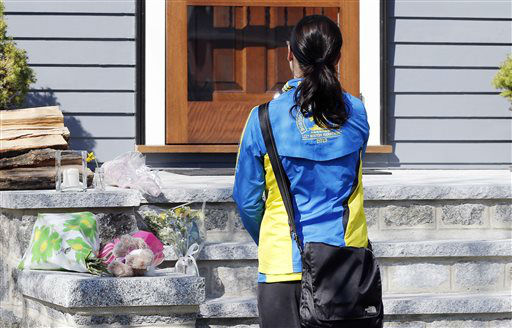 Runner Megan Cloke pauses after placing flowers on the doorstep of the Richard house in the Dorchester neighborhood of Boston,Tuesday, April 16, 2013. Martin Richard,8, was killed in Mondays&#39; bombings at the finish line of the Boston Marathon. The boy?s mother, Denise, and 6-year-old sister, Jane, were badly injured.   <span class=meta>(AP Photo&#47; Michael Dwyer)</span>
