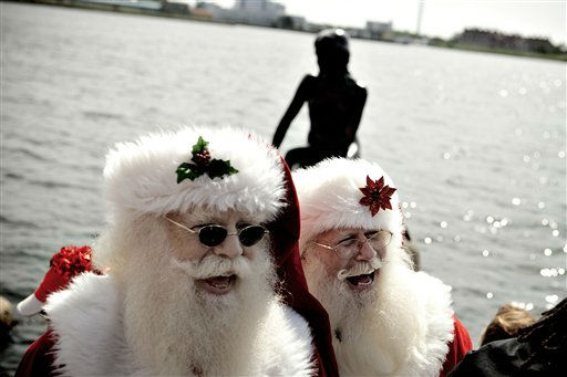 Participants laugh during the World Santa Claus Congress next to The Little Mermaid  statue in the harbour of Copenhagen, on Monday, July 18, 2011. The World Santa Claus Congress has taken place in the Dyrehavsbakken amusement park &#40;usually shortened to Bakken&#41; north of Copenhagen since 1957. &#40;AP Photo&#47;POLFOTO, Joachim Adrian&#41;  DENMARK OUT <span class=meta>(AP Photo&#47; ADRIAN JOACHIM)</span>