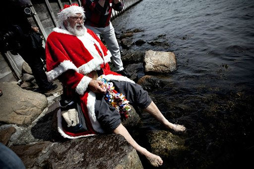 A Santa bathes his feet during the World Santa Claus Congress in front of  the Little Mermaid  statue in the harbour of Copenhagen, on Monday, July 18, 2011. The World Santa Claus Congress has taken place in the Dyrehavsbakken amusement park &#40;usually shortened to Bakken&#41; north of Copenhagen since 1957. &#40;AP Photo&#47;POLFOTO, Joachim Adrian&#41;  DENMARK OUT <span class=meta>(AP Photo&#47; ADRIAN JOACHIM)</span>