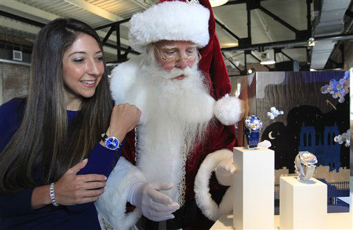 Brady White portrays Santa Clause, right, as he and model Marisa Neira show off his and hers &#34;Poetic Wish&#34; watches from Van Cleef &amp; Arpels during the unveiling of the Neiman Marcus 2012 Christmas Book in Dallas, Tuesday, Oct. 9, 2012.  The Van Cleef &amp; Arpels watches include a trip to Paris and Geneva that is priced for sale at &#36;1,090,000.  &#40;AP Photo&#47;LM Otero&#41; <span class=meta>(AP Photo&#47; LM Otero)</span>
