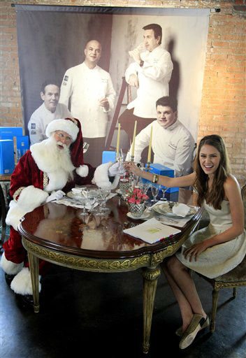Brady White, portraying Santa Clause, left, and model Kit Johnston display the private dinner for 10 gift with four world renowned chefs preparing the meal during the unveiling of the Neiman Marcus 2012 Christmas Book in Dallas, Tuesday, Oct. 9, 2012.  The meal that includes a Casa Dragones tequila tasting is priced for sale at &#36;250,000.  &#40;AP Photo&#47;LM Otero&#41; <span class=meta>(AP Photo&#47; LM Otero)</span>