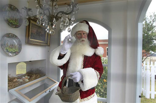 Santa Clause, portrayed by Brady White, gathers an egg from the Heritage Hen House Mini Farm on display during the unveiling of the Neiman Marcus 2012 Christmas Book in Dallas, Tuesday, Oct. 9, 2012. The Versailles-inspired Le Petit Trianon house including the chandelier in the hen house is priced for sale at &#36;100,000.  &#40;AP Photo&#47;LM Otero&#41; <span class=meta>(AP Photo&#47; LM Otero)</span>