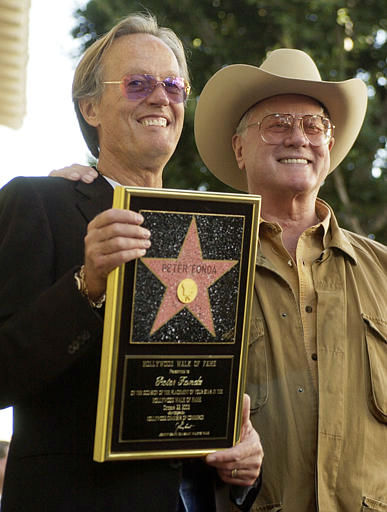 Actor-director Peter Fonda, left, is joined by actor Larry Hagman as he holds a replica of his new star on the Hollywood Walk of Fame in Los Angeles, Wednesday, Oct. 22, 2003. Hagman appeared in  <span class=meta>(AP Photo&#47; CHRIS PIZZELLO)</span>