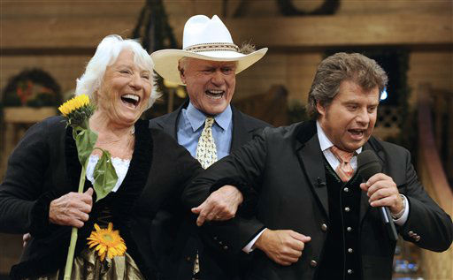 US actor Larry Hagman, center, his wife Maj, left,  and moderator Andy Borg, right, jokes during the  folk music broadcast &#34;Musikanten Stadl&#34; in the Olympic hall in Munich, southern Germany, on Friday, Sept. 19, 2008. The live broadcast of the &#34;Musikanten Stadl&#34; will take place on Saturday, Sept. 20, 2008.   <span class=meta>(AP Photo&#47; Christof Stache)</span>