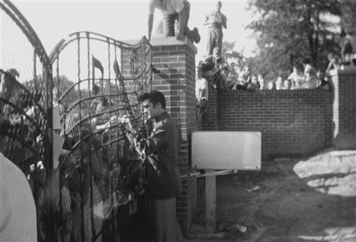 In this 1957 photo provided by Elvis Presley Enterprises, Inc and used by permission,  Elvis Presley greets fans at the gates of Graceland in Memphis, Tenn. Elvis Presley archivists have found three rare photos dating back to 1957 that show the young singer greeting fans at the gates of Graceland. Negatives of the photos were discovered as archivists pored through a vast collection of documents from the office of Vernon Presley, Elvis&#39; father. &#40;AP Photo&#47;Elvis Presley Enterprises, Inc&#41; NO SALES <span class=meta>(AP Photo&#47; Anonymous)</span>