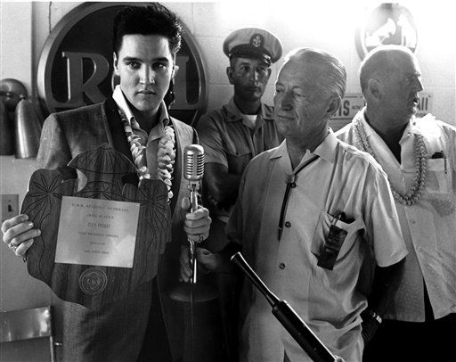 In this photo taken March 25, 1961 and provided by World War II Valor in the Pacific National Monument. Elvis Presley receives an award from members of  The pacific War Memorial Commission at the Hilton Hawaiian Village Hotel in Honolulu, Hawaii. Fifty years ago, Elvis Presley helped raise money and bring attention to help build the USS Arizona Memorial. The King is being asked to deliver one more time.  &#40;AP Photo&#47; Word War II Valor in the Pacific National Monument&#41; <span class=meta>(AP Photo&#47; Anonymous)</span>