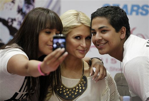 "<div class=""meta image-caption""><div class=""origin-logo origin-image ""><span></span></div><span class=""caption-text"">Paris Hilton poses for a photo with fans during her autograph signing session at a Sears in the Perisur Mall of Mexico City, Mexico, Tuesday March 29, 2011. Hilton is in Mexico to promote her new shoe line.    (AP Photo/ Eduardo Verdugo)</span></div>"