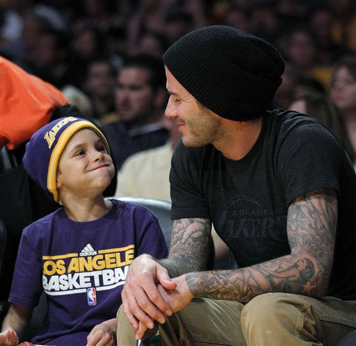 Soccer player David Beckham, right, looks at his son Romeo during an NBA basketball game between the Los Angeles Lakers and the Dallas Mavericks in Los Angeles,  Thursday, March 31, 2011.  <span class=meta>(AP Photo&#47; Jae C. Hong)</span>