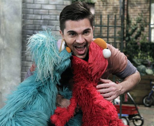 Colombian musician Juanes poses for photos with Rosita, left, and Elmo on the set of &#34;Sesame Street,&#34; during the taping of his appearance on the show in New York,  Monday, April 11, 2011.   <span class=meta>(AP Photo&#47; Richard Drew)</span>
